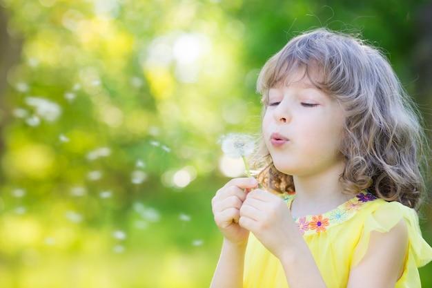 Glückliches kind bläst löwenzahnblume im freien mädchen, das spaß im frühlingspark hat