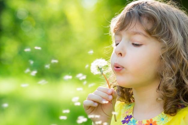 Glückliches kind bläst löwenzahnblume im freien mädchen, das spaß im frühlingstraum und -phantasie hat
