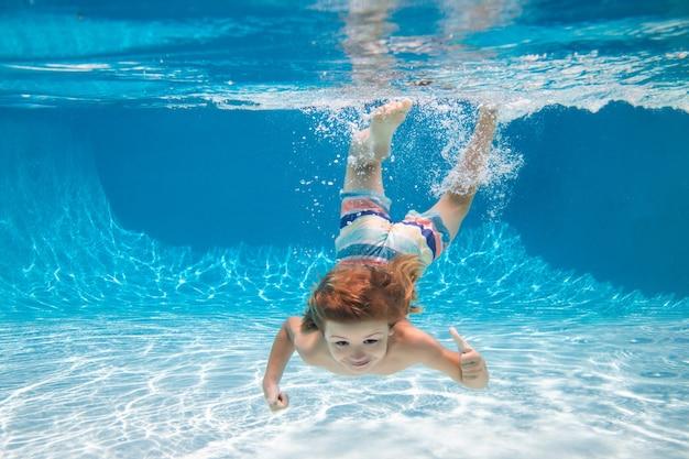 Glückliches kind, das am sommertag unter wasser im schwimmbad spielt. kinder spielen im tropischen resort. familienurlaub am strand. kinder schwimmen unter wasser.