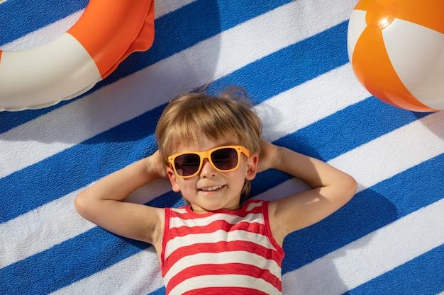 Glückliches kind, das auf gestreiftem handtuch im freien liegt. draufsichtporträt des kindes. lustiges baby lächelnd. sommerferienkonzept