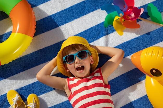Glückliches kind, das auf gestreiftem handtuch im freien liegt