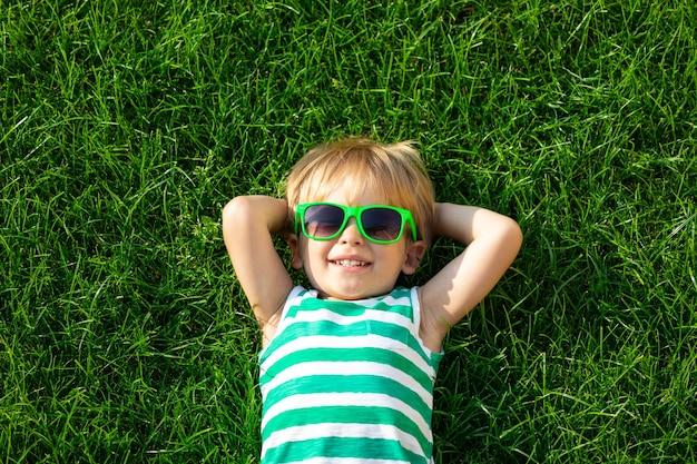 Glückliches kind, das auf grünem gras liegt. lächelnder junge, der spaß im freien im frühlingsgarten hat
