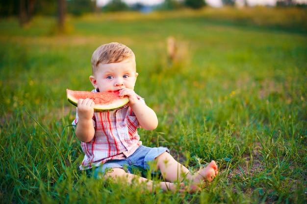 Glückliches kind, das auf grünem gras sitzt und draußen im frühjahr park der wassermelone gegen natürliche wand isst