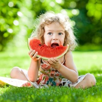 Glückliches kind, das auf grünem gras sitzt und wassermelone im freien im frühlingspark gegen natürlichen sonnigen unscharfen hintergrund isst