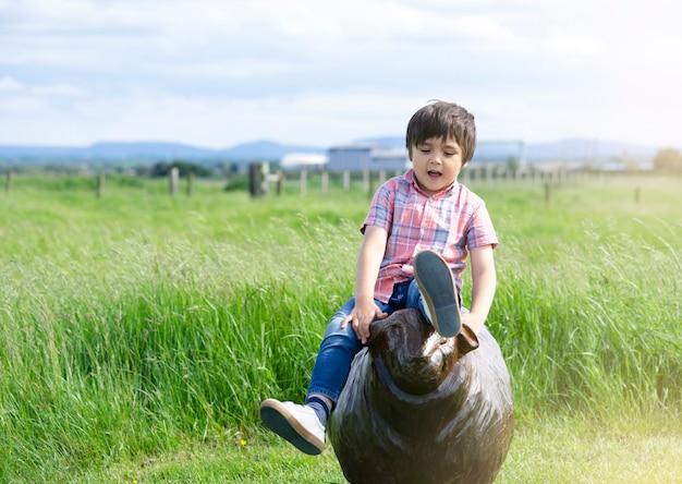 Glückliches kind, das auf hölzerner statue im park, aktiver kinderjunge draußen spielt an der rasenfläche in sonntags-sommer, positives kinderkonzept sitzt