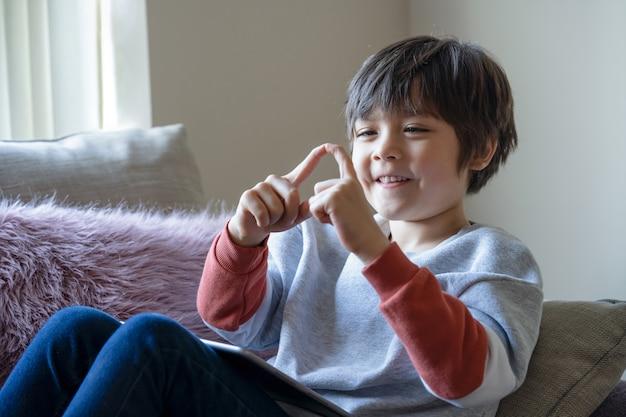 Glückliches kind, das auf sofa sitzt, das mit seinen fingern spielt, während cartoon auf tablette betrachtet