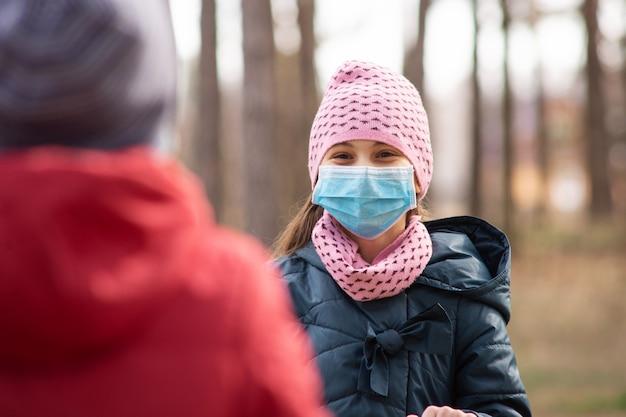 Glückliches kind, das auf spielplatz spielt, der medizinische maske trägt, um sich vor dem gefährlichen covid-19-virus zu schützen, gefährliches spielen während des ausbruchs des coronavirus