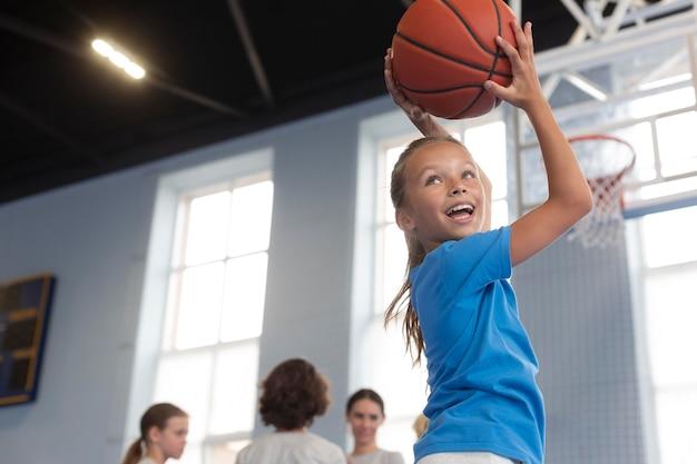 Glückliches kind, das basketball spielt