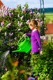 Glückliches kind, das blumen im garten wässert