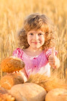 Glückliches kind, das brot gegen gelbes herbstweizenfeld hält