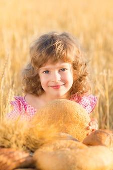 Glückliches kind, das brot in den händen gegen gelbes herbstweizenfeld hält