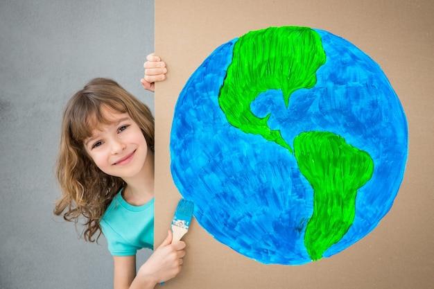 Glückliches kind, das den karton mit blauer farbe malt. kind hat spaß zu hause. frühjahrssanierungskonzept