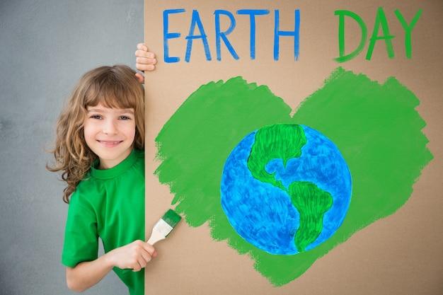Glückliches kind, das den karton mit grüner farbe malt. kind hat spaß zu hause. frühlings-erde-feiertagskonzept