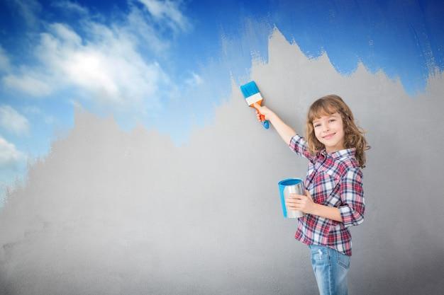 Glückliches kind, das die wand mit blauer farbe malt. kind hat spaß zu hause. frühjahrssanierungskonzept
