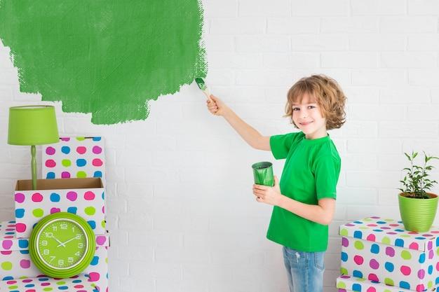 Glückliches kind, das die wand mit grüner farbe malt. kind hat spaß zu hause. frühjahrssanierungskonzept