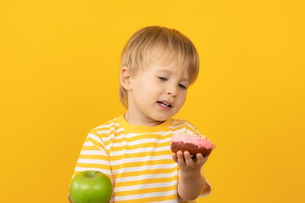 Glückliches kind, das donut und apfel gegen gelbe wand hält.