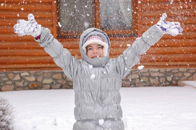 Glückliches kind, das draußen mit schnee, winterspiele im urlaub im landhaus spielt