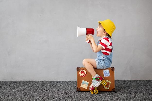 Glückliches kind, das draußen spielt. lächelndes kind, das von sommerferien und reisen träumt. vorstellungskraft und freiheitskonzept