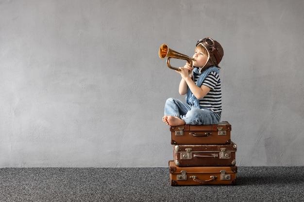Glückliches kind, das draußen spielt. lächelndes kind, das von sommerferien und reisen träumt.