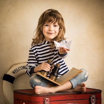 Glückliches kind, das drinnen mit papiersegelboot spielt. reise- und abenteuerkonzept