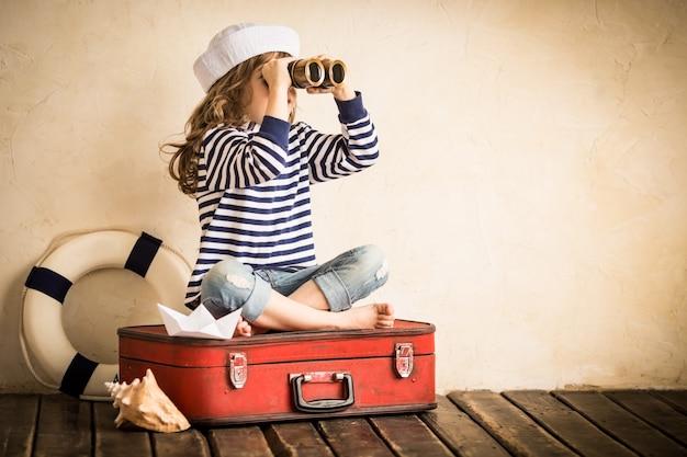 Glückliches kind, das drinnen mit spielzeug-segelboot spielt. reise- und abenteuerkonzept