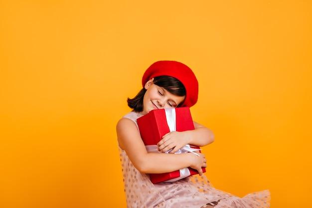 Glückliches kind, das geburtstagsgeschenk umarmt. fröhliches kleines mädchen mit geschenk.