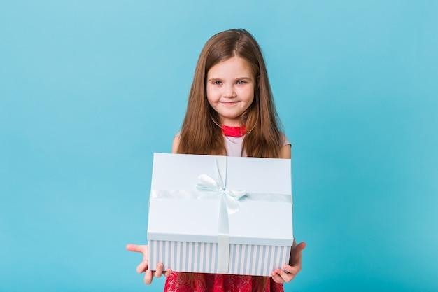 Glückliches kind, das geburtstagsgeschenke auf einer blauen wand hält Premium Fotos