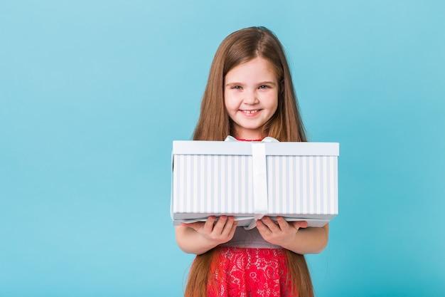 Glückliches kind, das geburtstagsgeschenke auf einer blauen wand hält