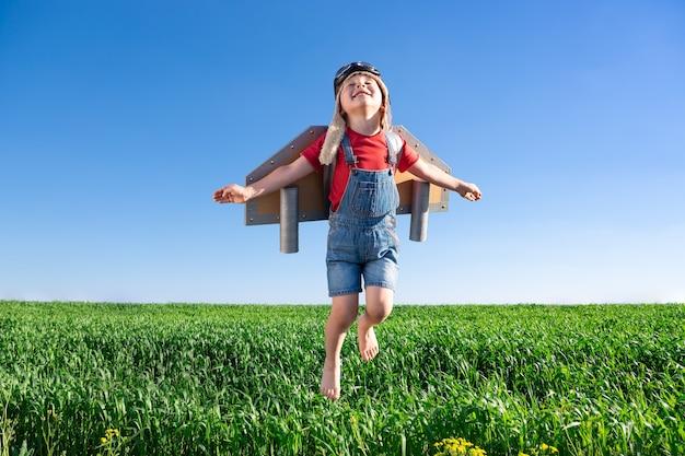 Glückliches kind, das gegen blauen himmel springt. kind, das spaß im frühlingsgrünfeld im freien hat. porträt des jungen mit papierflügeln. freiheits- und vorstellungskonzept