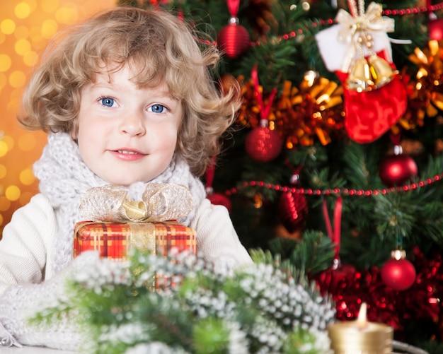 Glückliches kind, das geschenk gegen weihnachtsbaum mit dekorationen hält