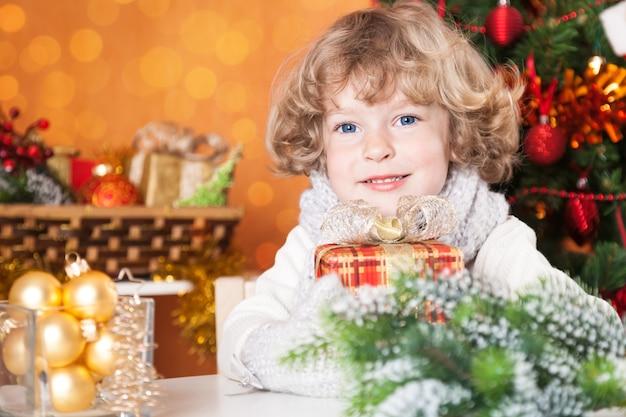 Glückliches kind, das geschenkbox gegen weihnachtsbaum mit dekorationen hält