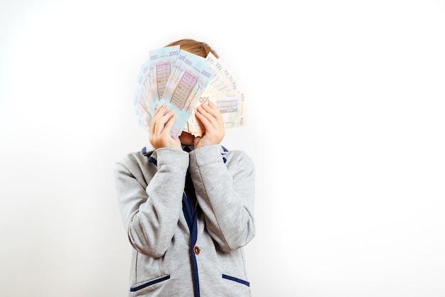 Glückliches kind, das gesicht hinter fan von geldscheinen versteckt. lottogewinner, geschäftsmann, erfolg. geld sparen.