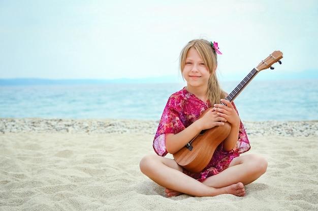Glückliches kind, das gitarre durch das meer griechenland auf naturhintergrund spielt