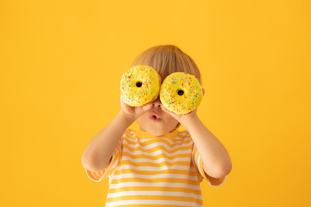 Glückliches kind, das glasierten donut gegen gelbe wand hält