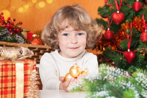 Glückliches kind, das goldene kugeln gegen verzierten weihnachtshintergrund hält