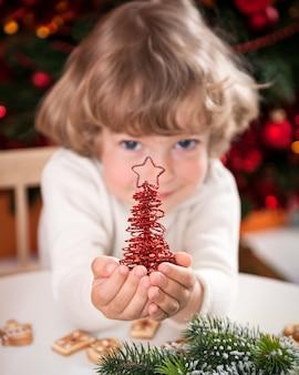 Glückliches kind, das handgemachte dekoration gegen weihnachtsbeleuchtung hält. fokus auf vordergrund