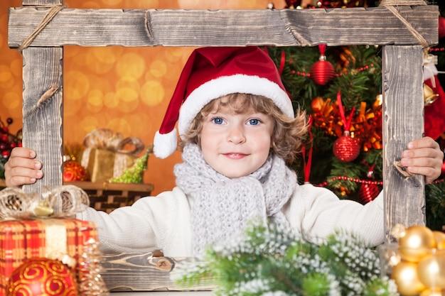 Glückliches kind, das holzrahmen gegen weihnachtsbaumhintergrund hält
