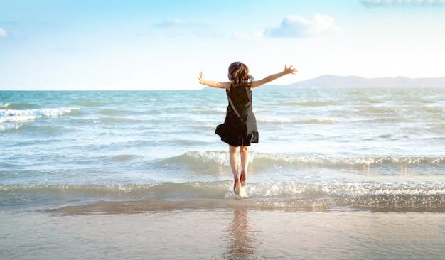 Glückliches kind, das im sommer auf den strand springt