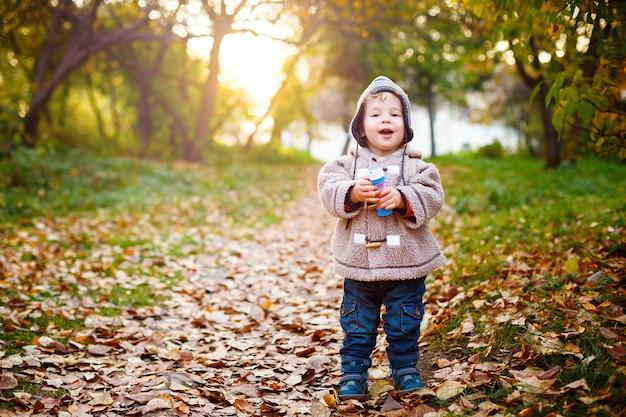 Glückliches kind, das in den park lacht und geht