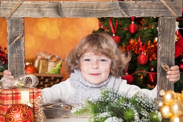 Glückliches kind, das in holzrahmen gegen verzierten weihnachtsbaumhintergrund schaut