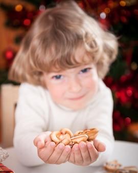 Glückliches kind, das kekse gegen weihnachtsbeleuchtung hält. konzentriere dich auf die hände
