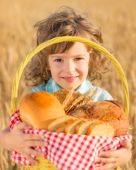 Glückliches kind, das korb mit brot im gelben herbstweizenfeld hält