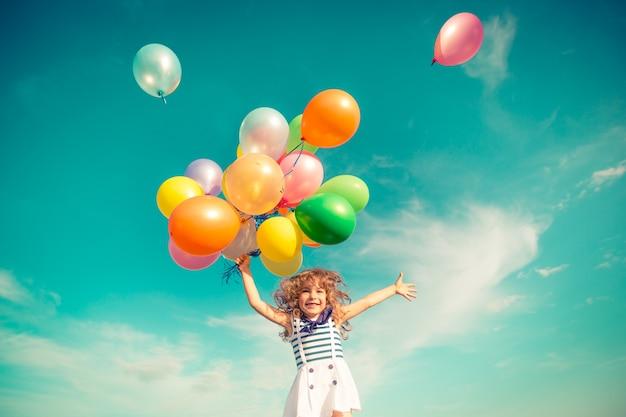 Glückliches kind, das mit bunten spielzeugballons draußen springt. lächelndes kind, das spaß im grünen frühlingsfeld gegen hintergrund des blauen himmels hat. freiheitskonzept