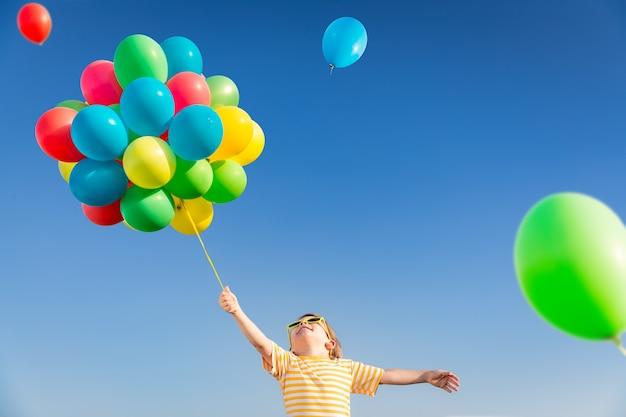 Glückliches kind, das mit hellen mehrfarbigen luftballons im freien spielt