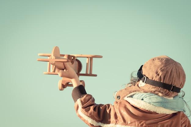 Glückliches kind, das mit hölzernem spielzeugflugzeug gegen herbsthimmelhintergrund spielt. retro-getönt