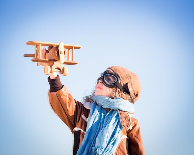 Glückliches kind, das mit hölzernem spielzeugflugzeug gegen winterhimmelhintergrund spielt