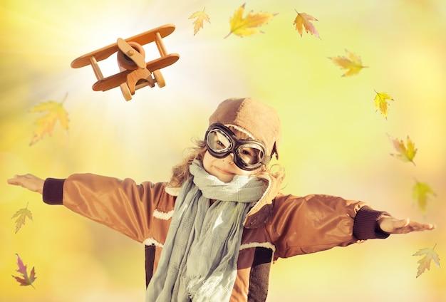 Glückliches kind, das mit hölzernem spielzeugflugzeug und fallenden ahornblättern gegen herbsthintergrund spielt