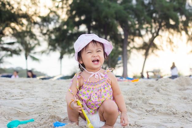 Glückliches kind, das mit sand am strand im sommer spielt
