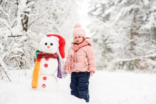Glückliches kind, das mit schneemann spielt. lustiges kleines mädchen auf einem spaziergang im winter im freien