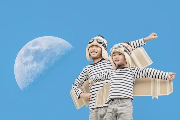 Glückliches kind, das mit spielzeugflügel gegen sommerhimmelhintergrund spielt.